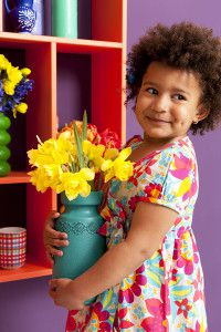 Young Girl Carrying Vase of Daffodils