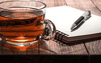Hot Tea with Notebook and Pen on Wooden Table