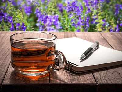 Hot Tea with Notebook and Pen on Wooden Table in Flower Garden